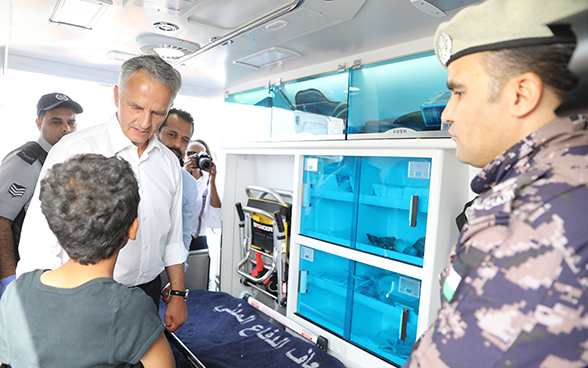 The Federal Councillor talks to a young boy in the ambulance donated by Switzerland to Jordan's civil defence agency