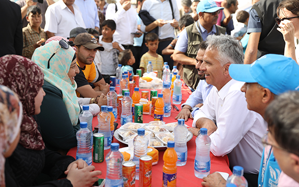 Didier Burkhalter and Azraq camp residents sitting around a table having a drink.