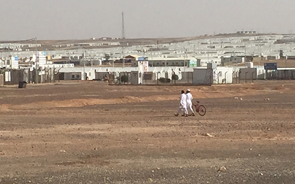 Two men, one of whom is pushing a bike, walk towards the Azraq refugee camp.