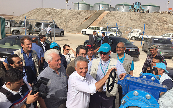 Federal Councillor Didier Burkhalter turns a wheel to switch on the drinking water supply network for the Azraq camp