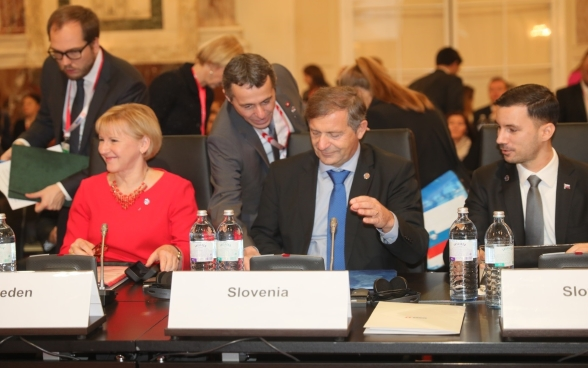Federal Councilor Ignazio Cassis approaches the Foreign Ministers of Sweden and Slovenia, Margot Wallström and Karl Erjavec.