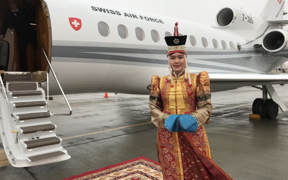 A woman in traditional dress poses in front of the Swiss Air Force plane at Ulaanbaatar airport