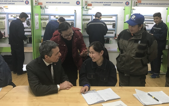 Federal Councillor Cassis in conversation with three Mongolian apprentices.