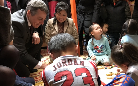 Federal Councillor Cassis plays in a school with Mongolian children.