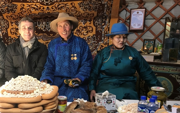 Federal Councillor Cassis sits at a richly laid table with two Mongolian cattle breeders.