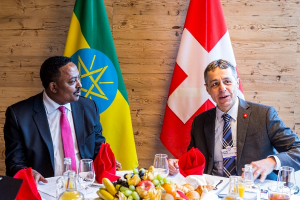 Federal Councillor Cassis is sitting at a richly covered table in conversation with Ethiopian Foreign Minister Gebeyehu. The flags of Switzerland and Ethiopia can be seen in the background.